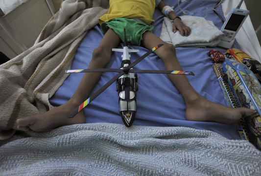 A toy helicopter is placed between the legs of a boy undergoing treatment at the paediatric cancer section of the Hospital Escuela in Tegucigalpa