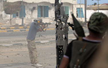 An anti-Gaddafi fighter fires a rocket propelled grenade (RPG) during clashes with Gaddafi forces at the front line in the center of Sirte
