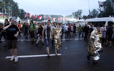 People evacuate Pukkelpop outdoor music festival after a tent collapsed following a heavy storm near Hasselt