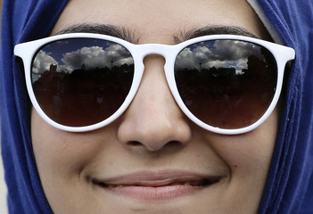 Blue sky and clouds are reflected in the sunglasses of a protester during a demonstration to express solidarity with migrants and to demand the government welcome refugees into Britain, in London