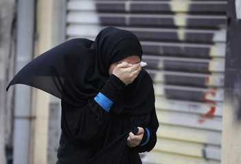 An anti-government protester runs covering her eyes from tear gas fired by riot police during a rally in support of human rights activist Abdulhadi al-Khawaja, in Manama