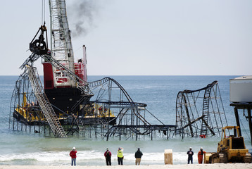 Workers use a crane to remove remnants of a roller coaster that have been left in the ocean after Superstorm Sandy hit Seaside Heights last year, in New Jersey