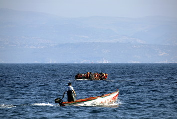 A Greek fisherman powers his boat as a dinghy overcrowded with Syrian refugees approaches the Greek island of Lesbos