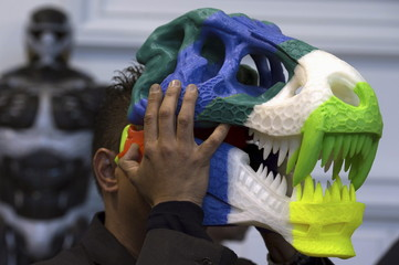 A 3D printing professional wears his T-Rex skull creation during a 3D printing show in Brussels