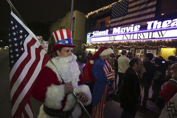 """Ornstein holds an American flag as fans line up at the Silent Movie Theatre for a midnight screening of """"The Interview"""" in Los Angeles, California"""