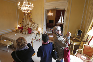 Visitors take pictures of furniture displayed for auction in a bedroom at the Hotel de Crillon in Paris