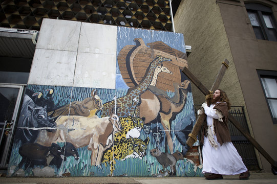 """Michael Grant, 28, """"Philly Jesus,"""" carries a 12 foot cross 8 miles past a mural depicting Noah's Ark in North Philadelphia towards LOVE Park in Center City as part of a Christmas walk to spread the true message of the holiday in Philadelphia"""