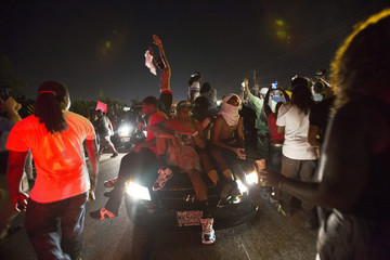 People sit on a car during a peaceful demonstration, as communities react to the shooting of Michael Brown in Ferguson