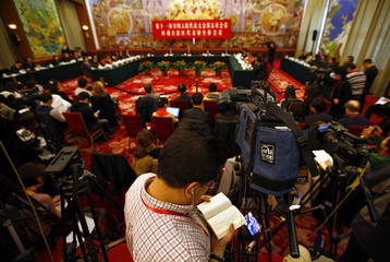 A cameraman reads a book as he films the meeting between the Tibetan provincial delegation and representatives from the NPC in Beijing