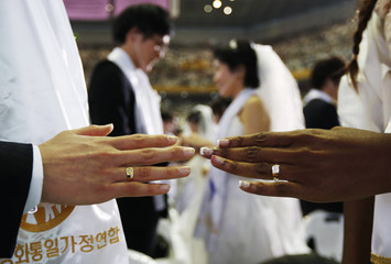 A newlywed couple poses for photographs with their wedding rings during a mass wedding ceremony of the Unification Church at Cheongshim Peace World Centre in Gapyeong