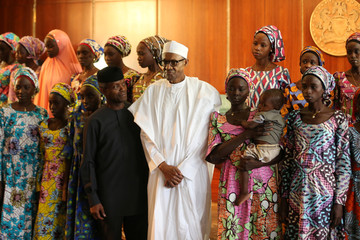 Some of the 21 Chibok schoolgirls released by Boko Haram pose during a group photograph with President Muhammadu Buhari and Vice President Yemi Osinbajo In Abuja, Nigeria