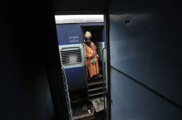 A Sikh passenger stands at the doorway of a train as he waits for electricity to be restored at a railway station in New Delhi