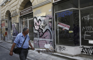 A lottery ticket vendor walks in front of a closed shop in central Athens