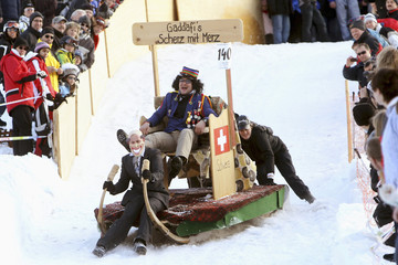 A team with participants dressed up as Switzerland's Finance Minister Merz and Libya's leader Gaddafi slides down the course on their sleigh during the 22nd Hornschlittenrennen sledge race in Alt St. Johann