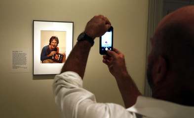 A visitor takes a picture of a photograph of Oscar-winning actor and renowned comedian Robin Williams displayed at the Smithsonian's National Portrait Gallery in Washington