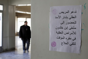 A piece of paper is seen on the wall of a building where patients of lbn Khaldoun psychiatric hospital were transferred to, in Aleppo