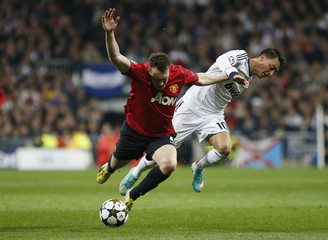 Manchester United's Phil Jones challenges Real Madrid's Mesut Ozil during their Champions League soccer match at Santiago Bernabeu stadium in Madrid