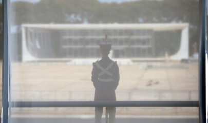 Soldier of the presidential guard with Supreme Court building in the background stands at Planalto Palace in Brasilia