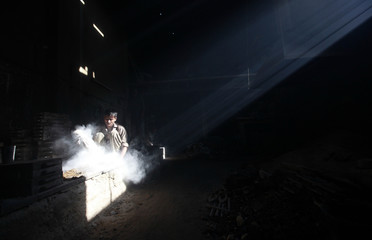 A beam of sunlight shines on Faizan, 22, a labourer working in a factory molding parts of irons, in Karachi