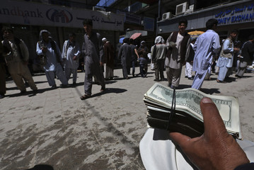 A money changer holds a stack of U.S. dollars at Kabul's largest money market