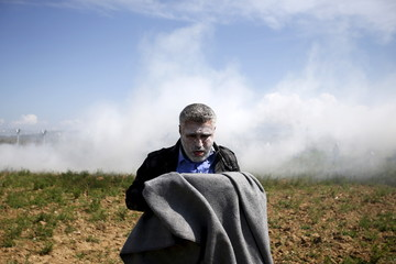 A migrant catches his breath after inhaling teargas thrown by Macedonian police on a crowd of more than 500 refugees and migrants protesting next to a border fence at a makeshift camp at the Greek-Macedonian border near the village of Idomeni