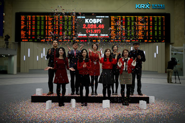 Employees of the Korea Exchange (KRX) pose in front of the final stock price index during a photo opportunity for the media at the ceremonial closing event of the 2016 stock market in Seoul