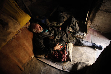 Former steel factory worker Zarko Hrgic lies with dogs at his home, a cave near Babina river in Babino village, near the central Bosnian town of Zenica