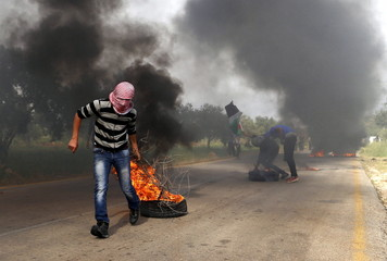 A Palestinian protester drags a burning tyre during clashes with Israeli troops in the West Bank village of Duma near Nablus