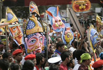People carry masks to celebrate the Bengali new year in Dhaka