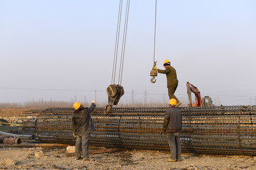 Hoisting steel bars in the construction site