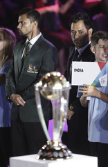 Bangladesh's captain Mashrafe Mortaza and India's captain Mahendra Singh Dhoni on stage near the World Cup trophy, during the ICC Cricket World Cup 2015 opening event at the Sidney Myer Music Bowl