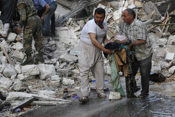 Men salvage belongings at a site hit by what activists said was a barrel bomb dropped by forces loyal to Syria's President Bashar al-Assad in Aleppo's Bustan al-Qasr neighborhood