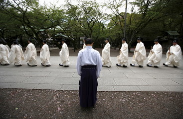 A staff member of the shrine bows as Shinto priests walk after a ritual to cleanse themselves during Annual Spring Festival at the Yasukuni Shrine in Tokyo