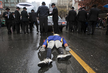 A group of B.C Lions fans drag a Winnipeg Blue Bomber scarecrow down the street during the 99th Grey Cup parade in Vancouver.