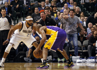 Mavericks' Cuban reacts as Carter guards Lakers' Bryant during the second half of their NBA basketball game in Dallas