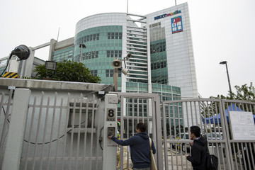 Employees wait to enter through a gate of Apple Daily and Next Media's headquarters in Hong Kong