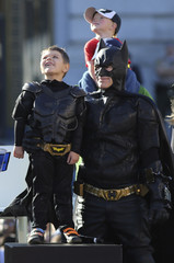 "Five-year-old leukemia survivor Miles Scott, dressed as ""Batkid"" looks to the sky as he stands next to Batman"