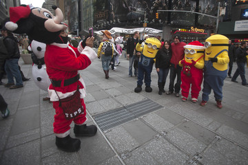 A man dressed up as Mickey Mouse takes a picture as people pose with others dressed up as Minion characters in Times Square in New York