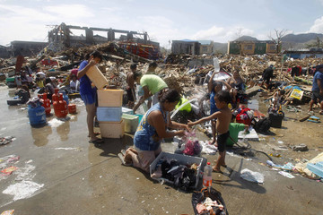 Survivors take baths and wash clothes with water from open faucet after strong winds brought by Typhoon Haiyan battered Tacloban city
