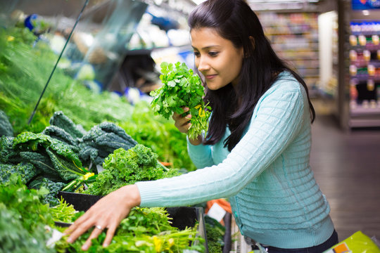 Closeup portrait, beautiful, pretty young woman in sweater picking up, choosing green leafy vegetables in grocery store