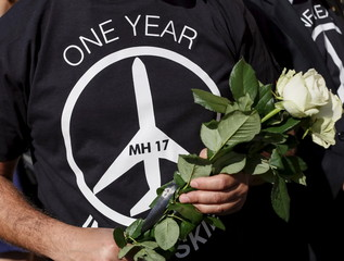 A man carries flowers outside the Dutch embassy to commemorate the victims of the downing of Malaysia Airlines MH17 in eastern Ukraine a year ago, in Kiev