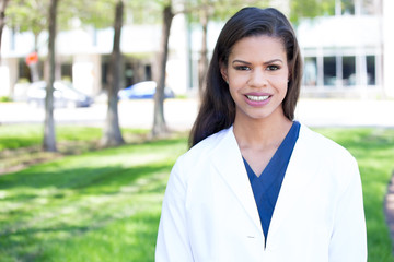 Closeup headshot portrait of friendly, smiling confident female, healthcare professional with lab coat, isolated outdoors outside background.