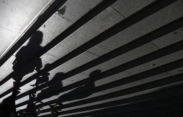 People cast shadows as they walk down the steps of St Paul's Cathedral in London