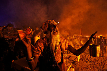 A Sadhu or a Hindu holy man plays a damru, a small two headed drum, as he offers prayers at the banks of the Ganga river on the occasion of the annual Hindu festival of 'Karthik Purnima' or full moon night, in Allahabad