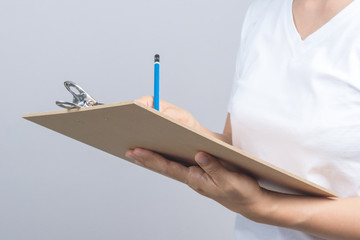 Woman hand holding wooden clipboard and a pen
