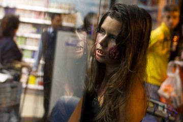 A girl dressed as a zombie looks into the window from outside a shop during a Zombie Walk in Caracas