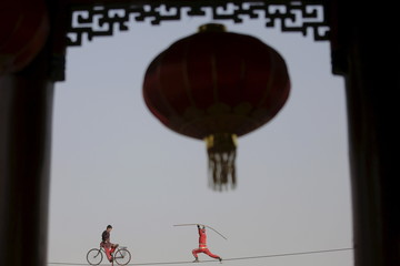Acrobats perform on a tightrope as the Chinese Lunar New Year which welcomes the Year of the Monkey is celebrated at Daguanyuan park in Beijing