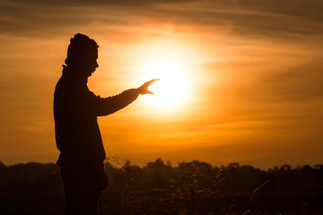 Silhouette of a man standing and rise his hands up in the air during sunset