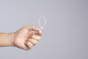 Hand holding self lock plastic cable