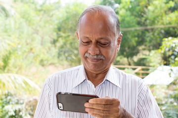 Closeup portrait, elderly gentleman in white striped shirt holding smartphone seeing good news text message, isolated outside outdoors background